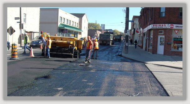 laying asphalt with assistance of road repair men
