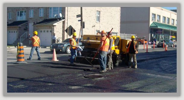 asphalt layer and men smoothing it out