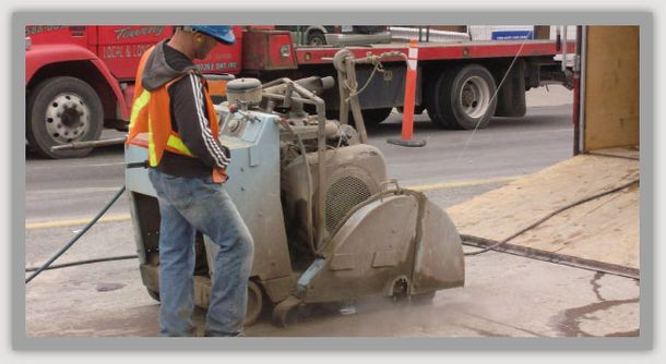 man cutting concrete with large drivable blade